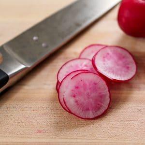 cut radishes on cutting board with knife