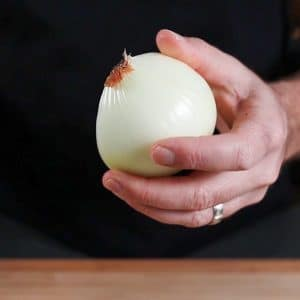 holding a peeled yellow onion