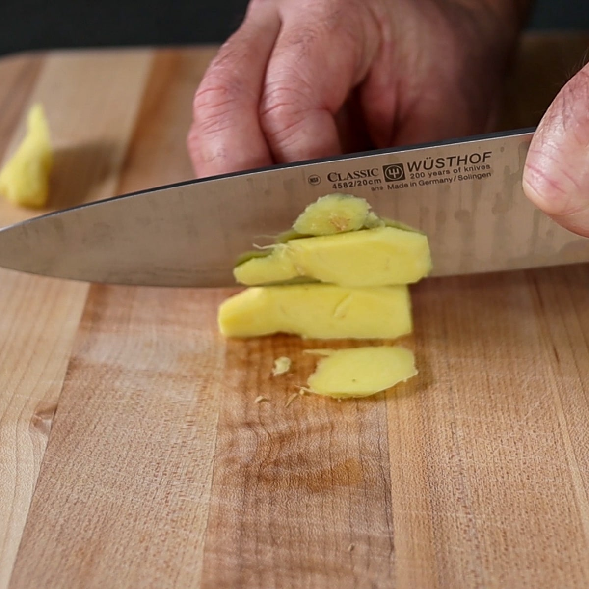 slicing ginger on cutting board