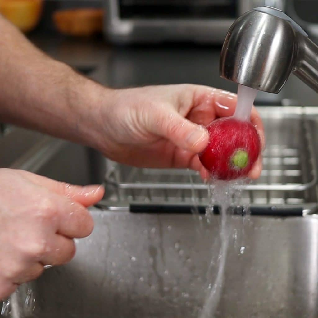 washing radish under cold water faucet