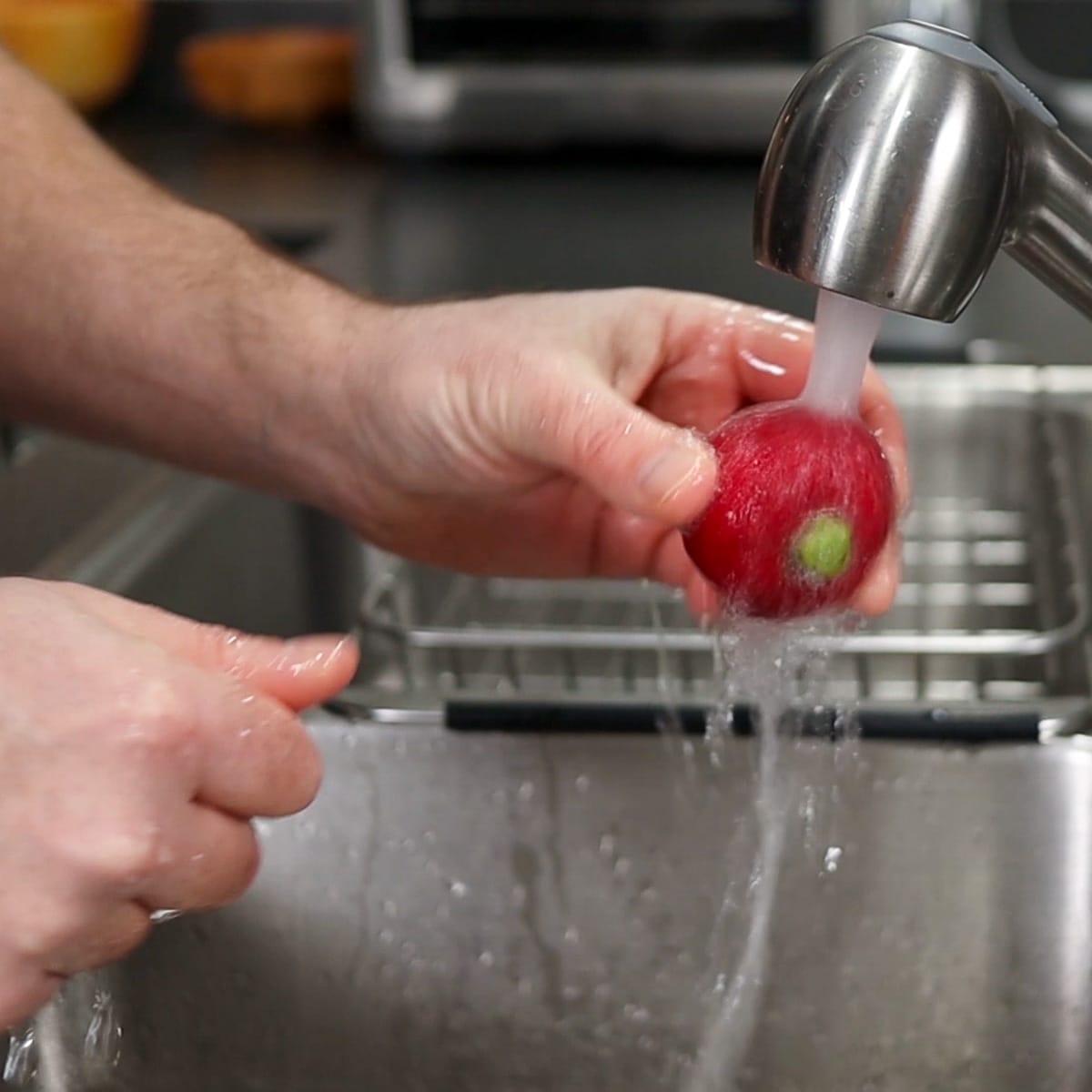 washing radish under cold water faucet