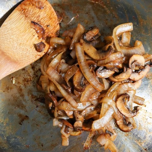 mushrooms and onions sauted in a pan