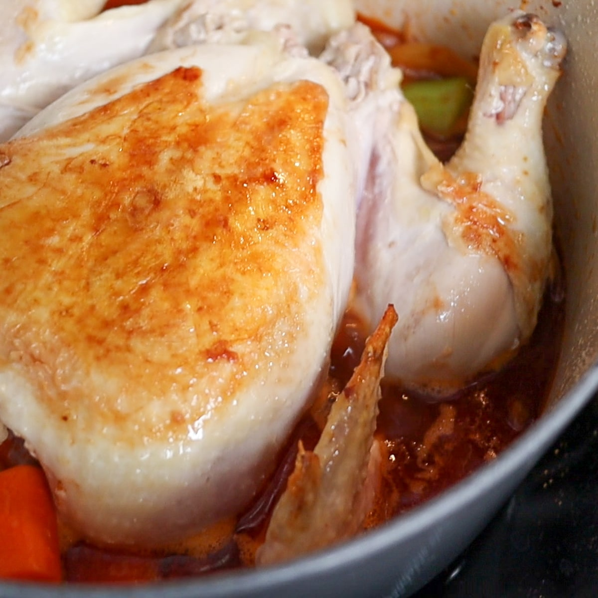 whole chicken braising in a pot