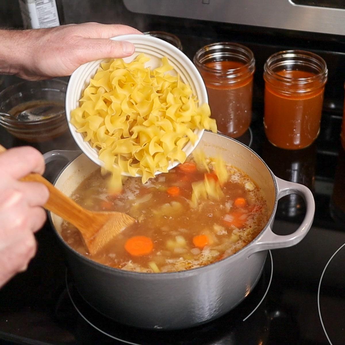 adding egg noodle to soup pot