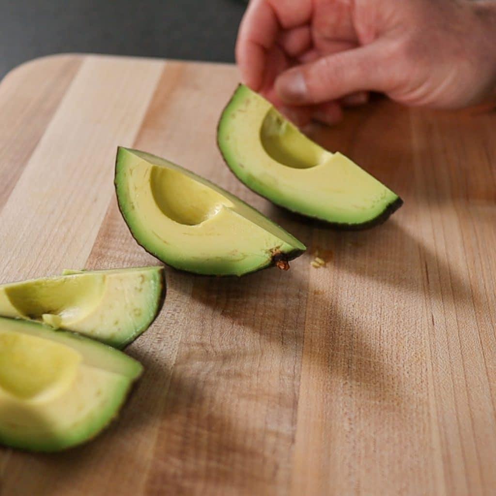 slicing the avocados into four pieces