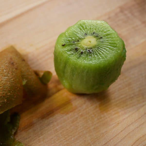 a kiwi fruit peeled on a cutting board