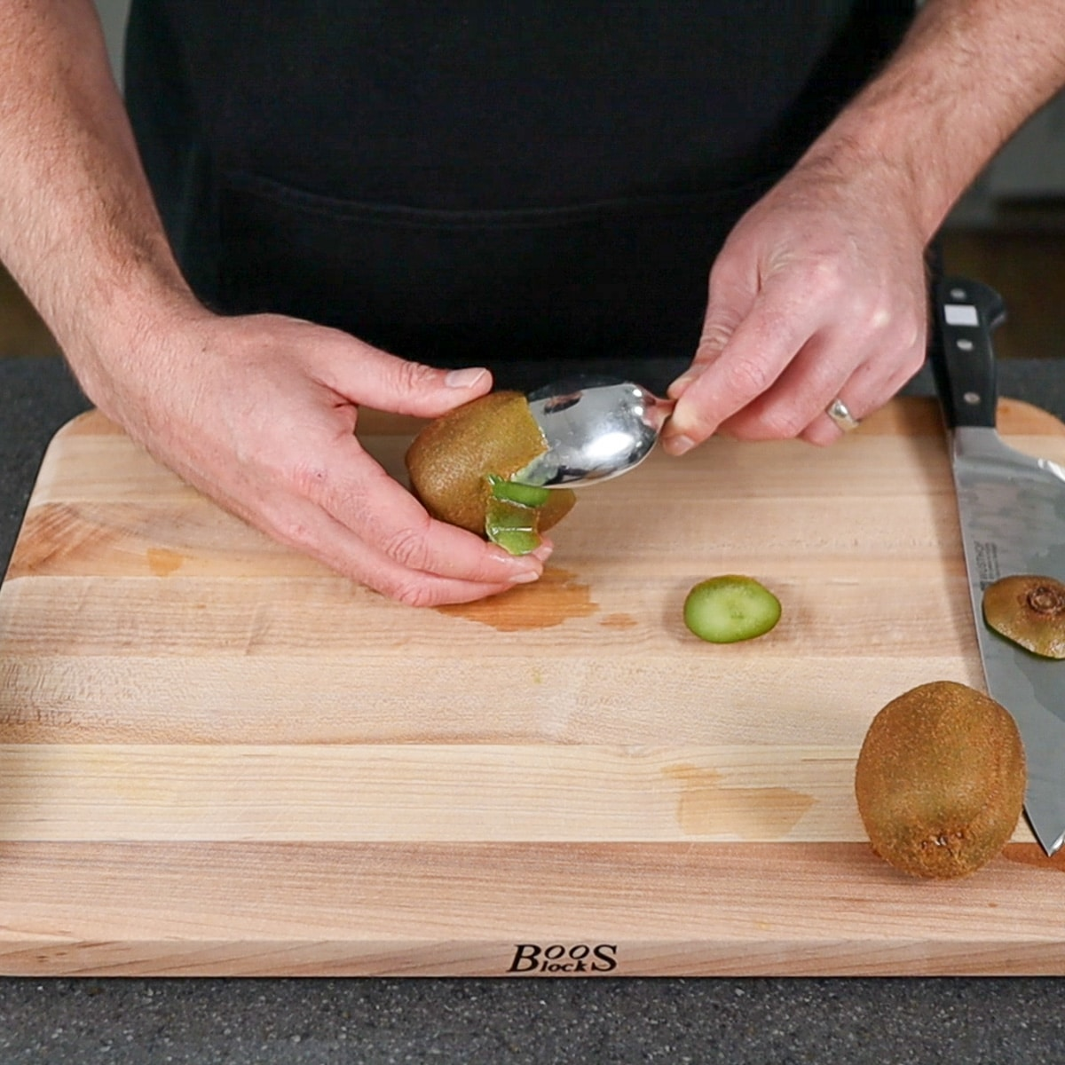 kiwi fruit being peeled with a spoon