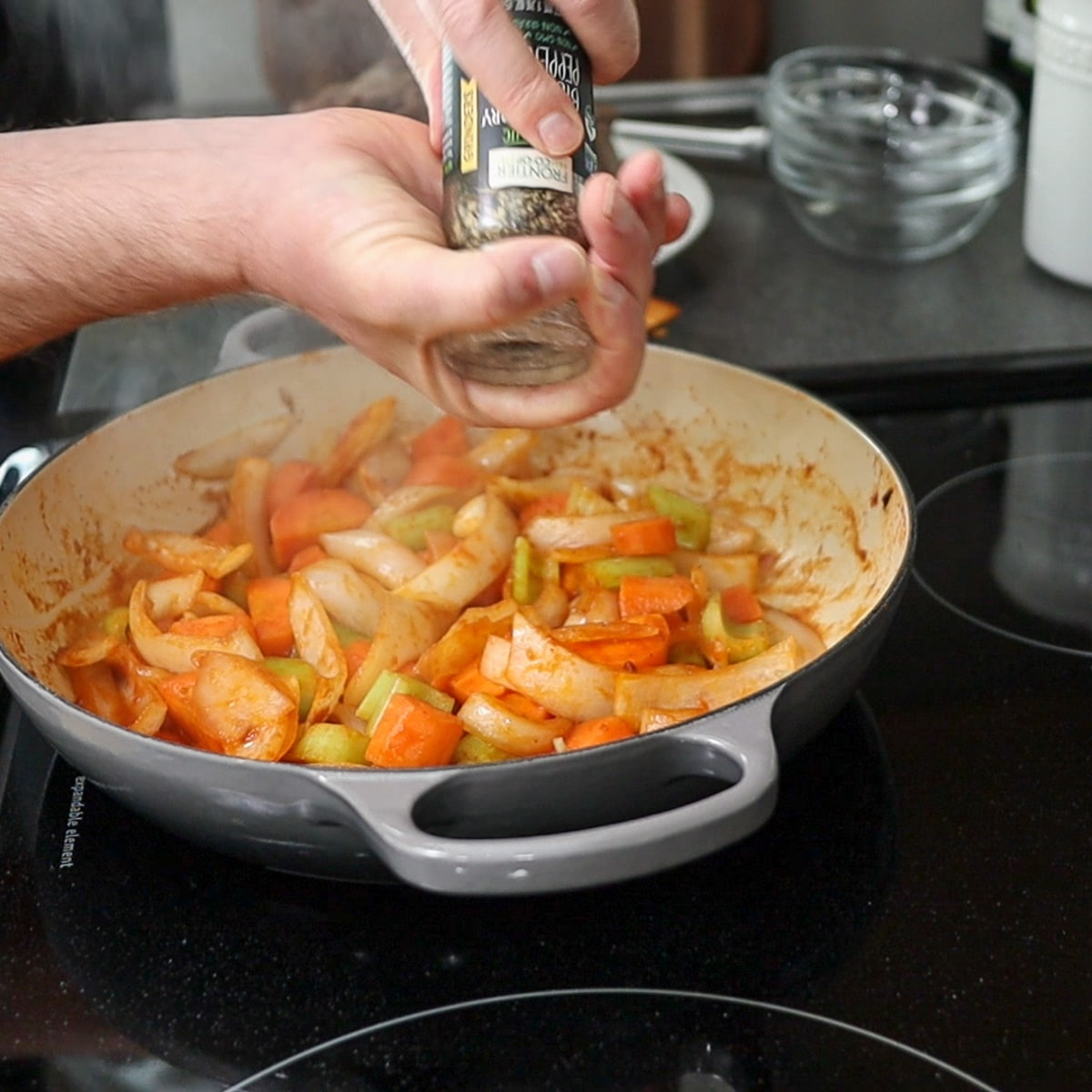 adding pepper to the vegetables