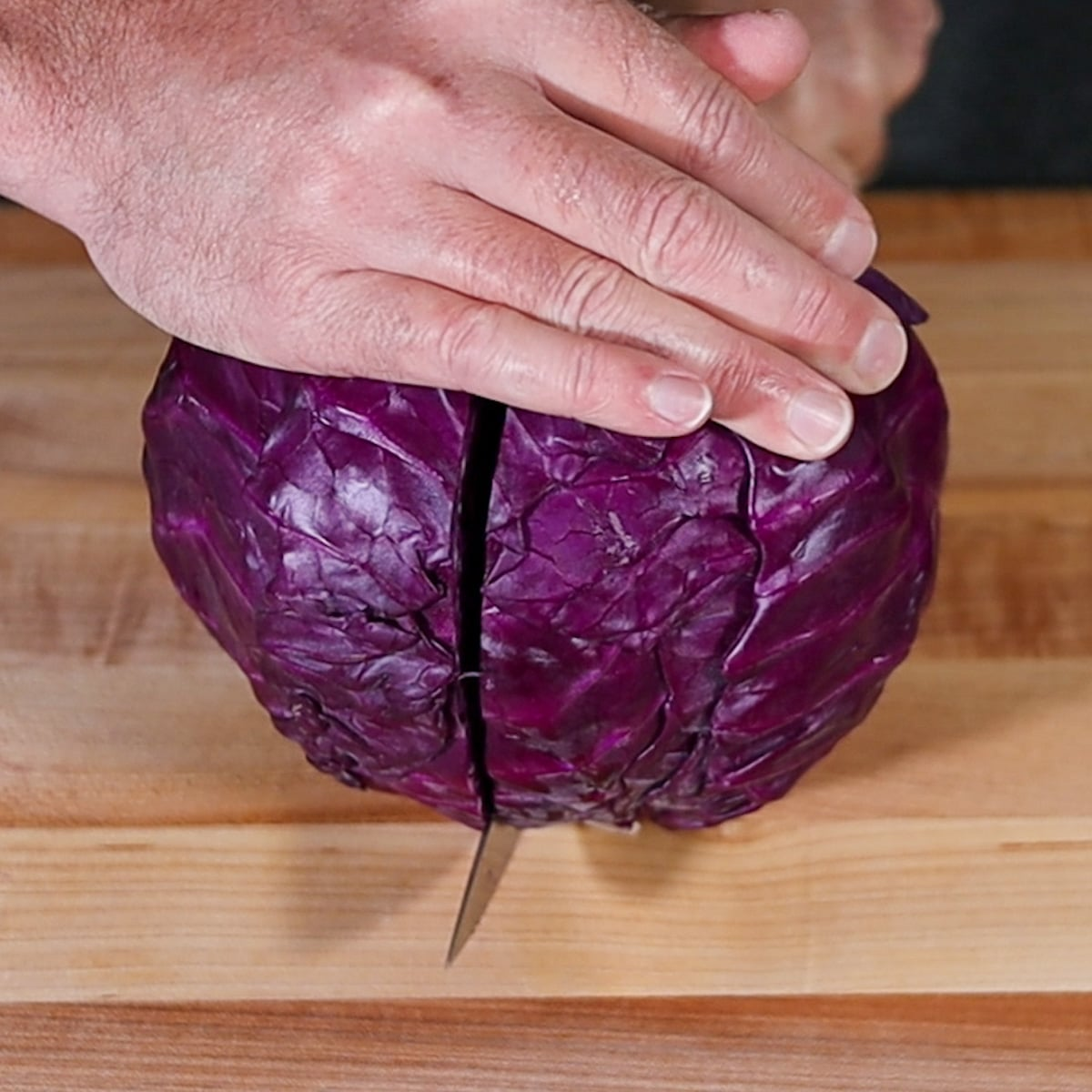 cutting a cabbage in half with a knife