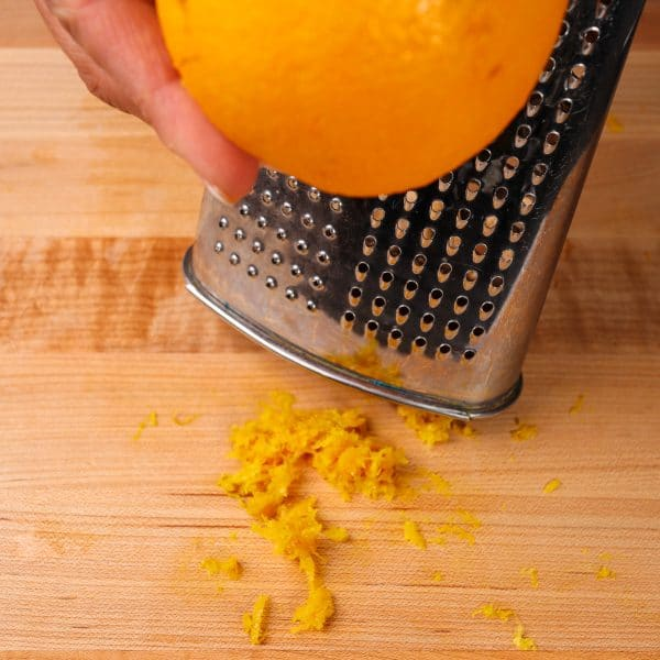 an orange being zested on a box grater