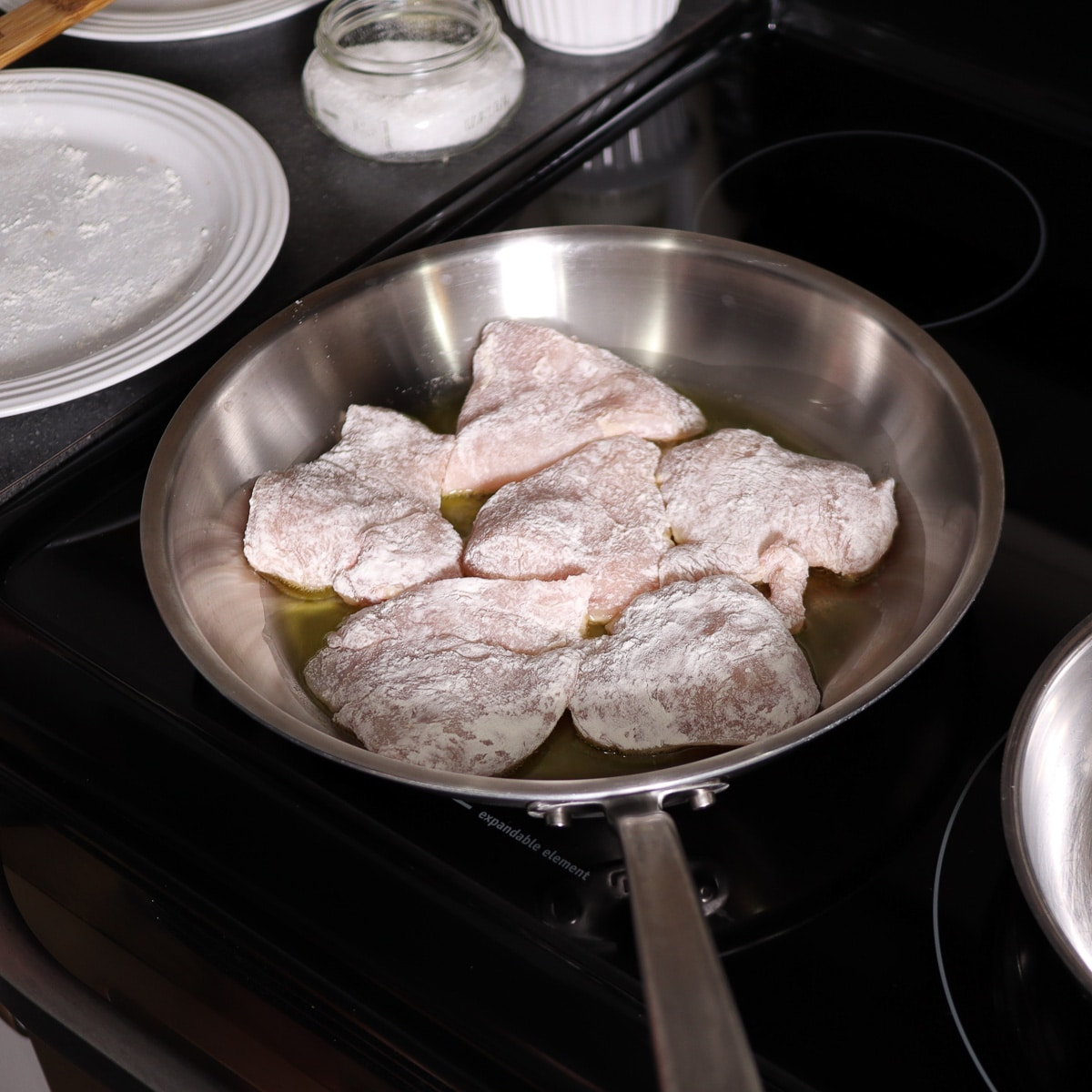 chicken that is floured added to preheated pan with oil