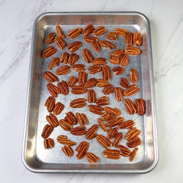 raw pecans on a sheet pan