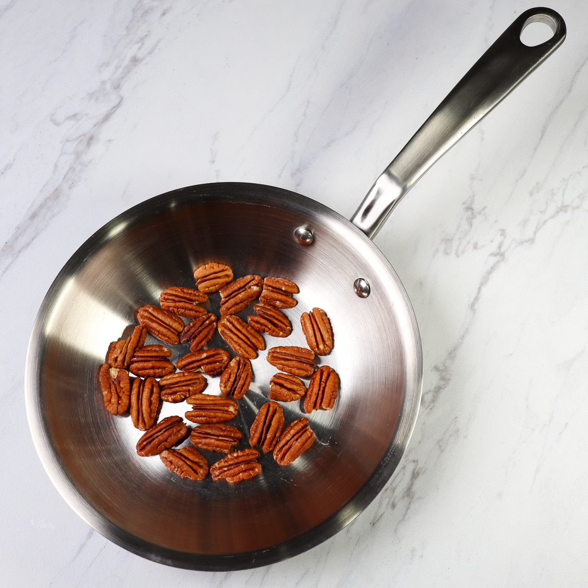 raw pecans in a frying pan