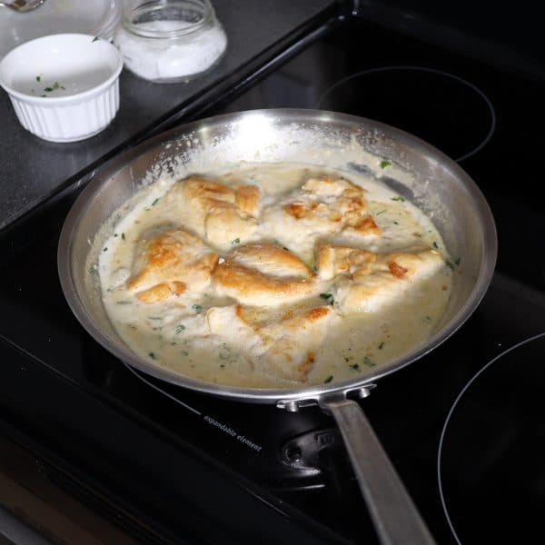 the chicken in a pan with the cream sauce simmering