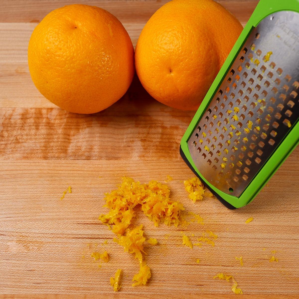 orange zest on a board with a microplane.
