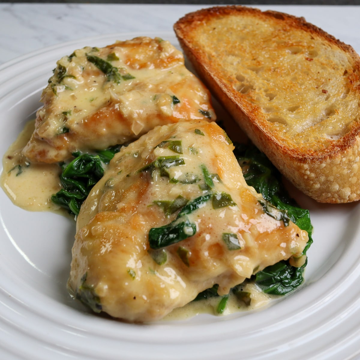 the final chicken florentine dish ready to be eaten on a white plate