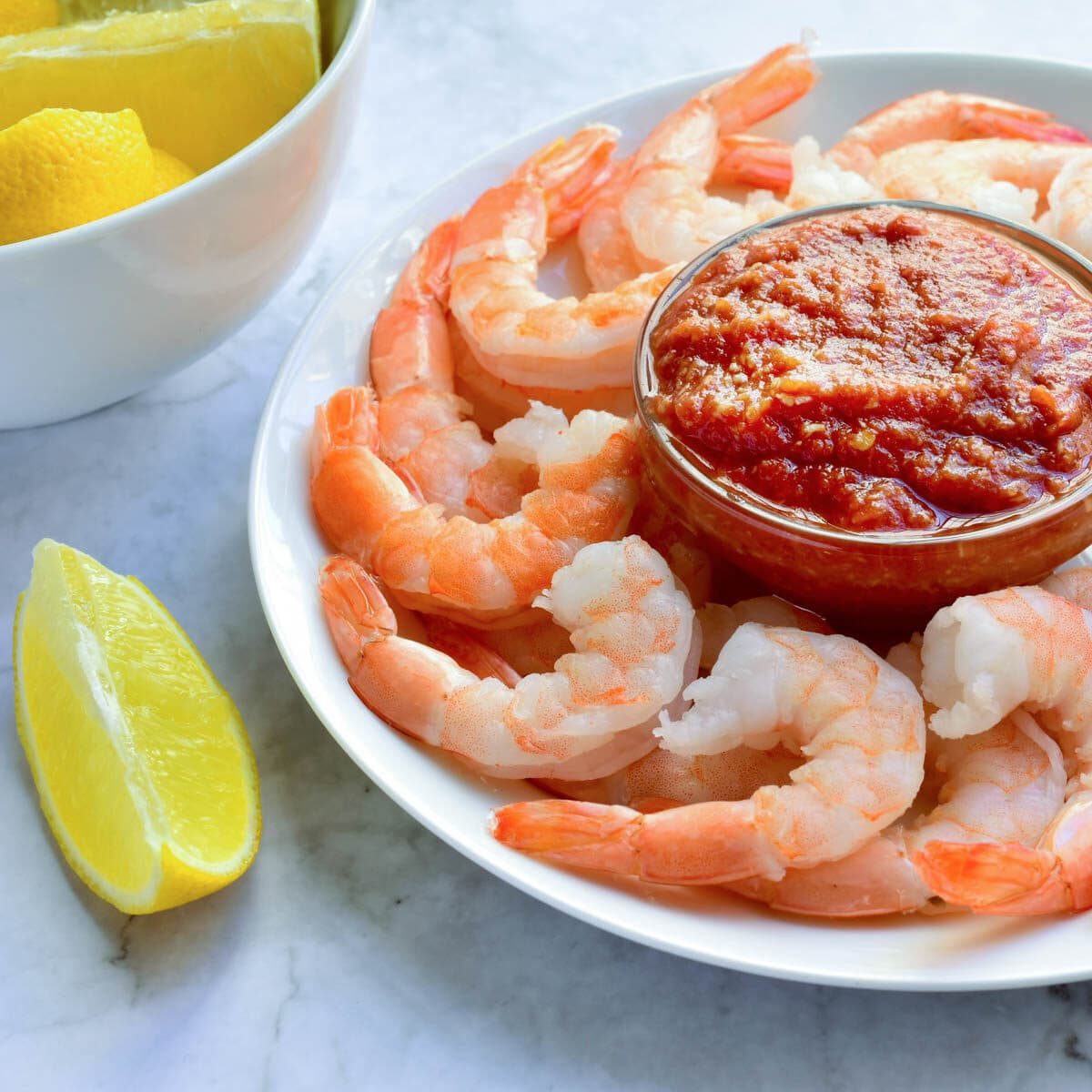 Plate with raw shrimp and cocktail sauce in a glass bowl and lemon wedges on the side.