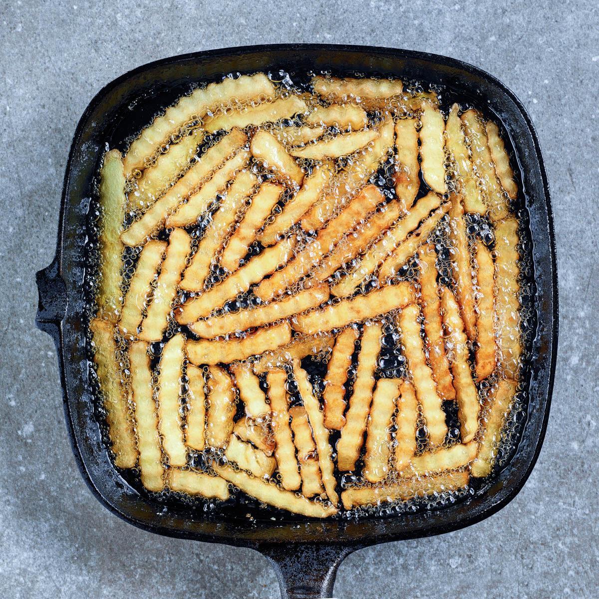 Crinkle fries in a frying pan in oil