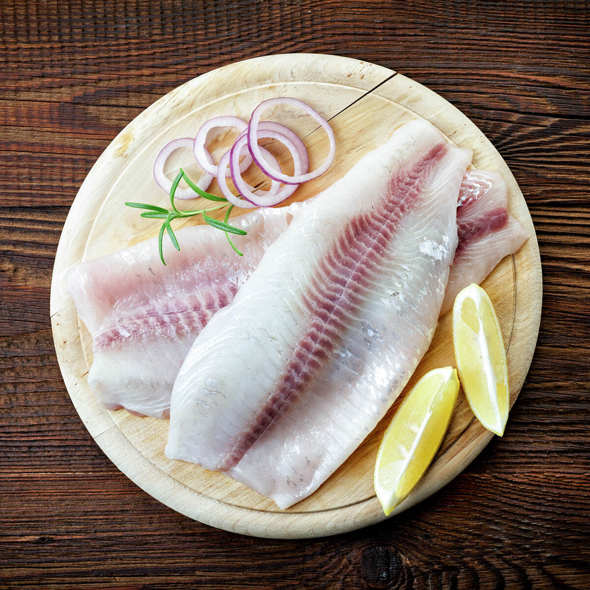 3 fresh fish filets on a round cutting board with raw red onion rings and lemon wedges.