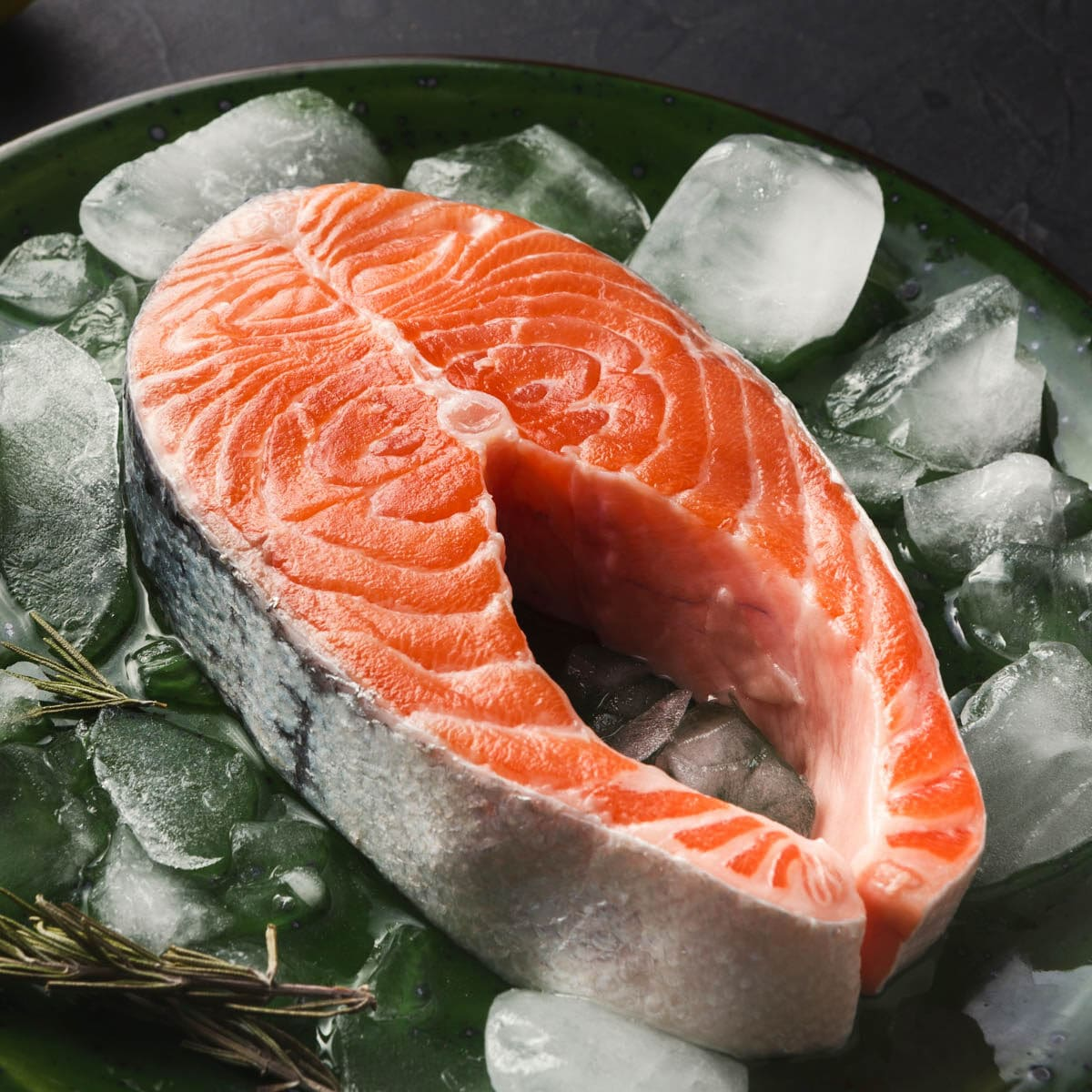 Raw salmon steak on a plate with ice