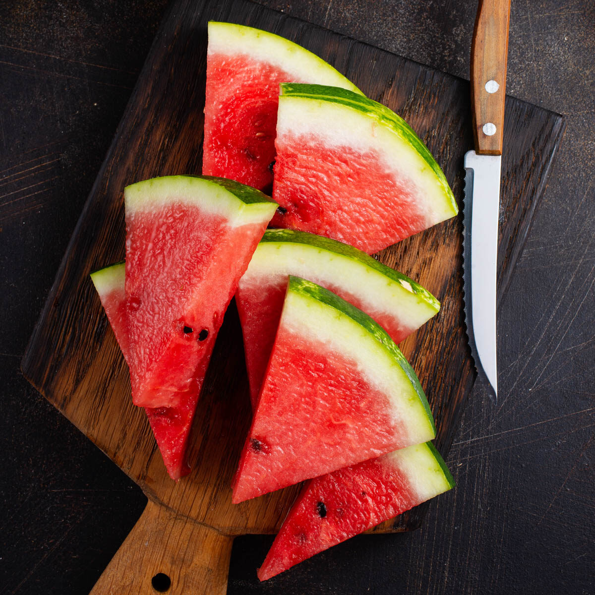 Watermelon sliced into triangles on a cutting board with a knife laying on the board.