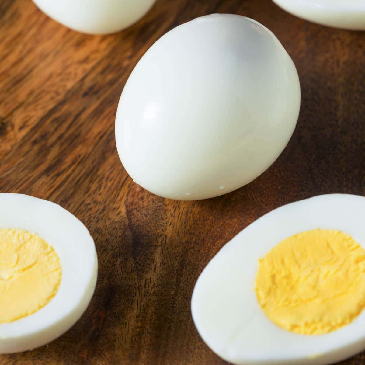 Hard boiled egg in the middle with a hard boiled egg cut in half in front