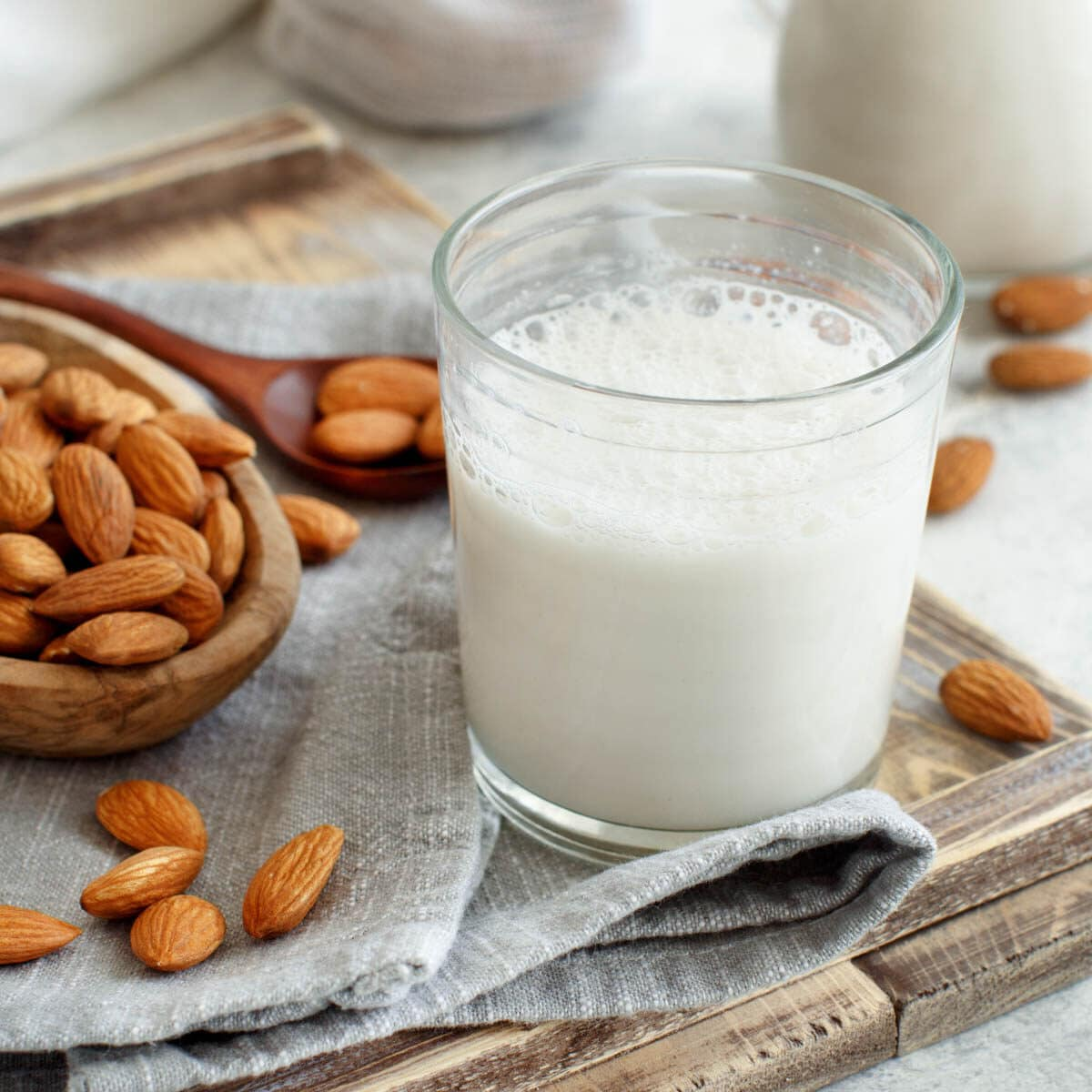 Glass of almond milk with a wooden bowl and spoon full of almonds