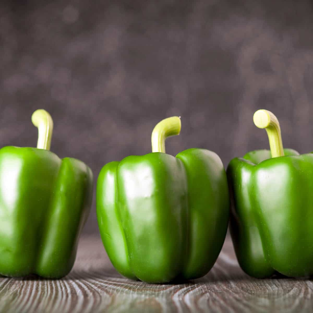 3 whole green bell peppers lined up
