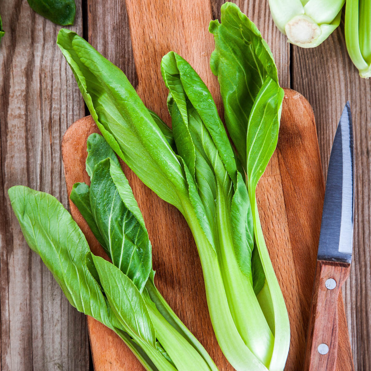 2 bunches of bok choy on a cutting board with a paring knife next to them.
