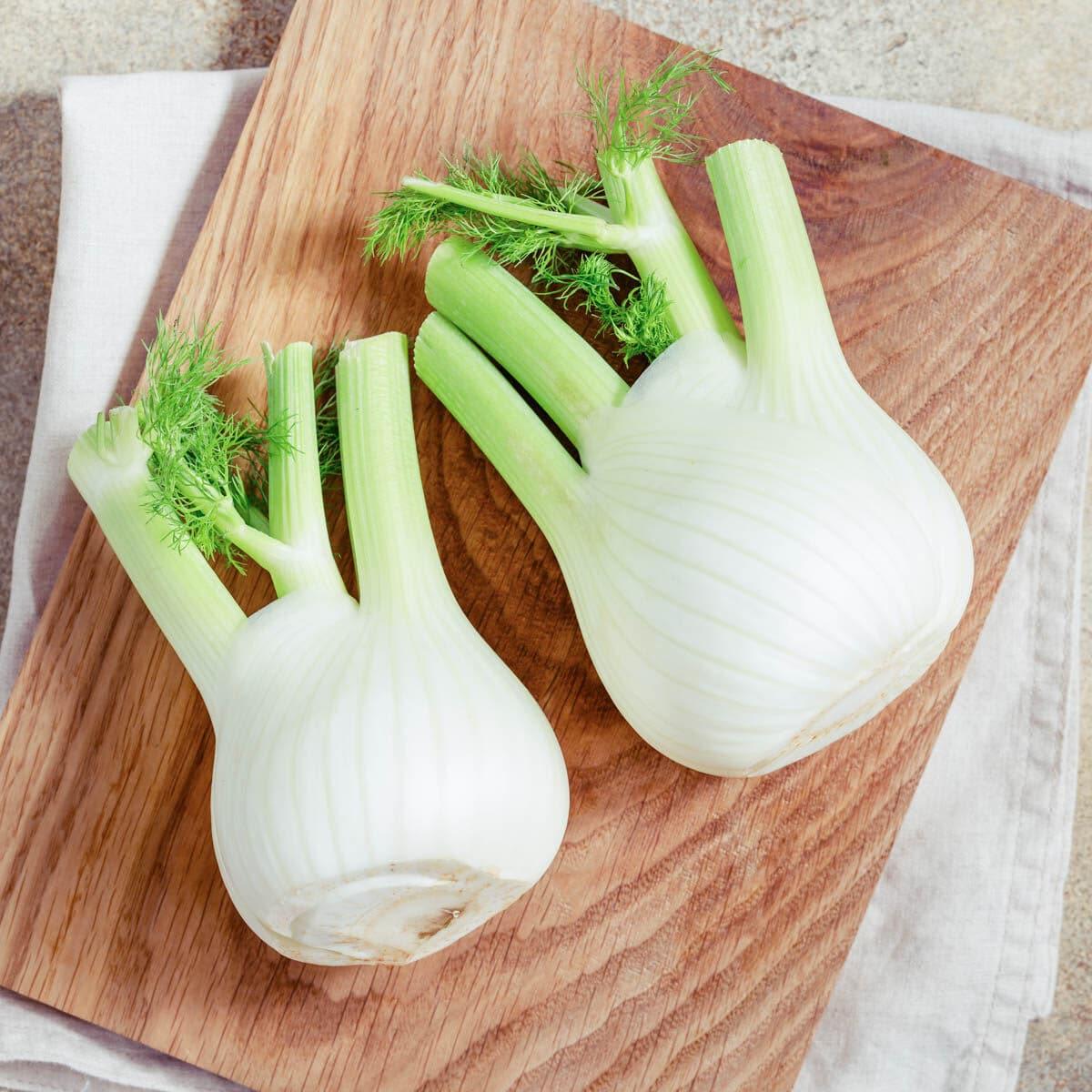 2 fennel stocks laying on a cutting board.