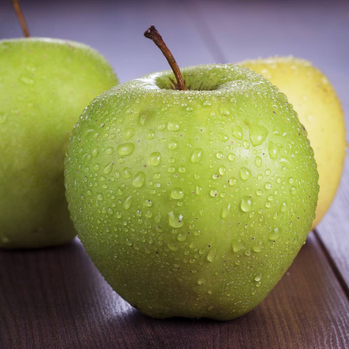 3 green apples with water beads all over them.