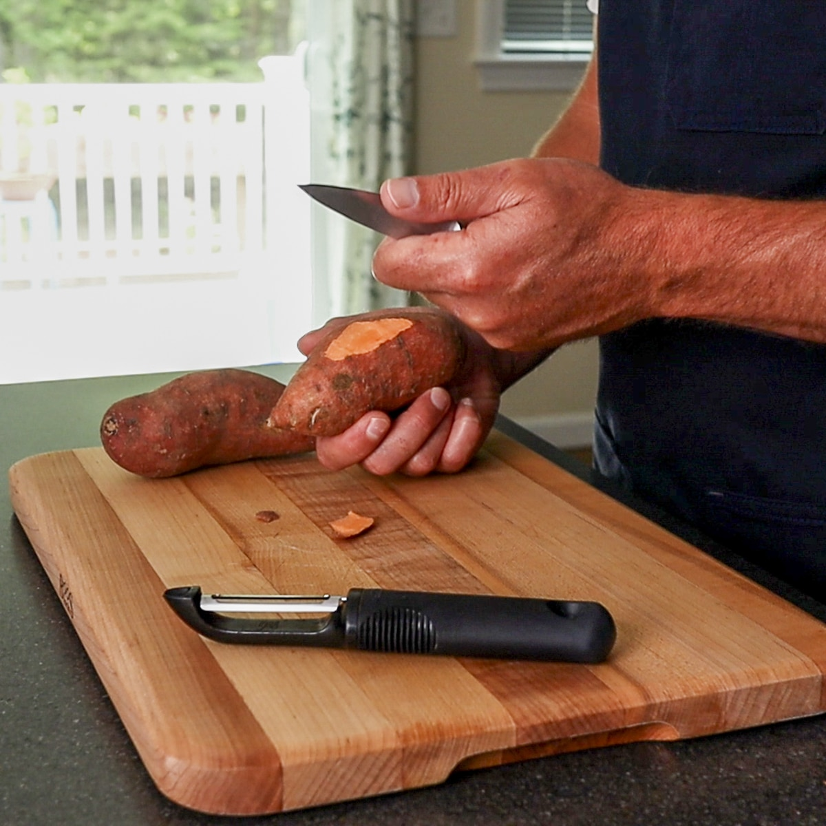 using a pairing knife and a peeler to peel a potato.