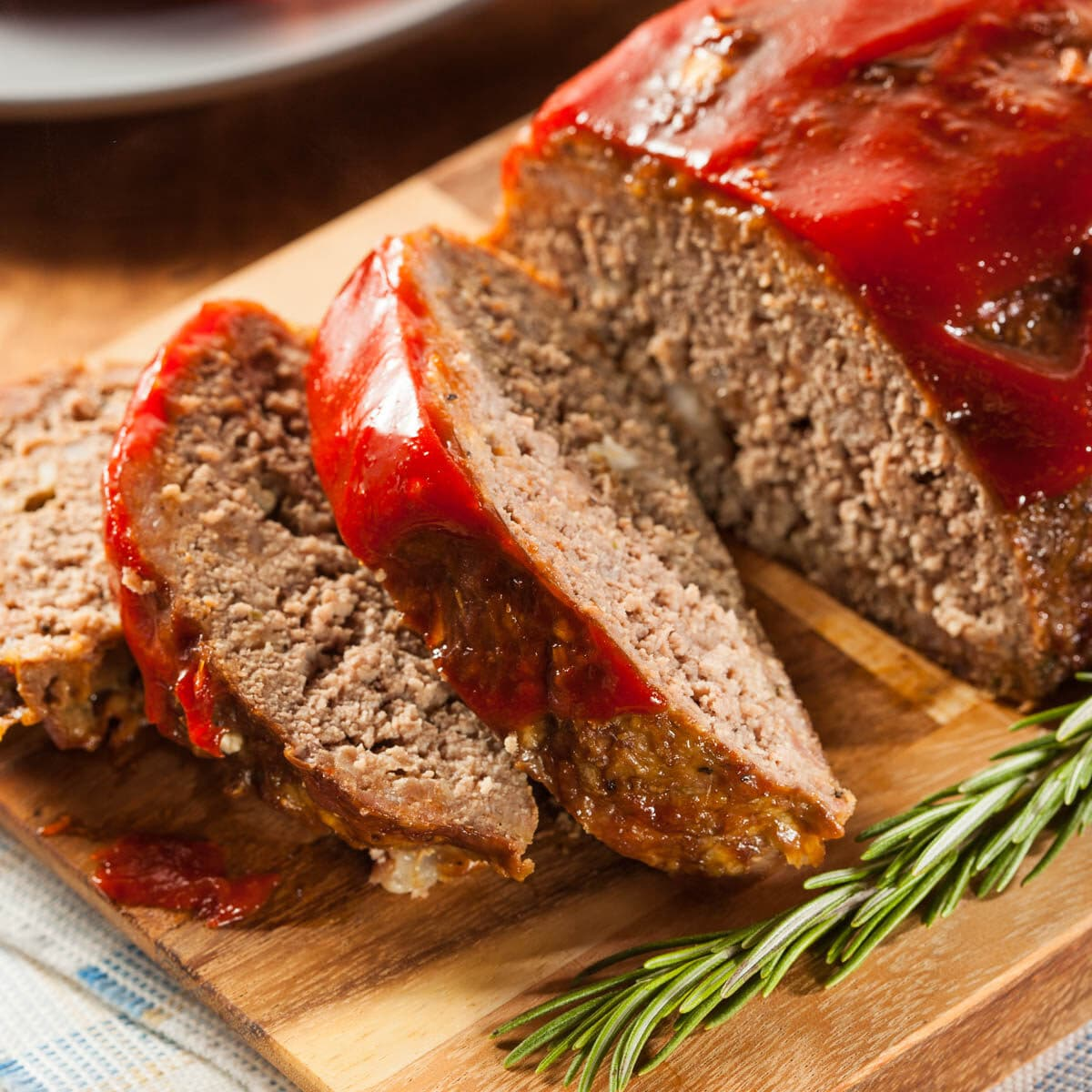 Meatloaf on a cutting board with 3 cut slices